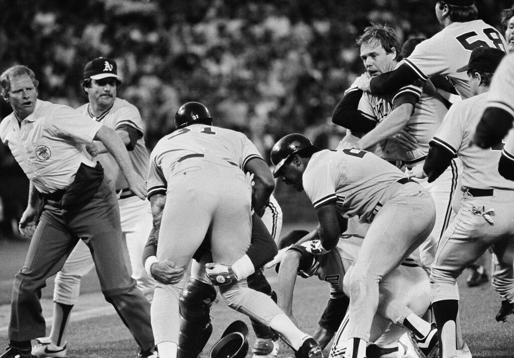 . New York Yankees Dave Winfield is held by back Oakland A\'s catcher Mike Heath after Winfield charged A\'s pitcher Steve McCatty, right, with a brush back pitch in the second inning, May 26, 1984 at the Oakland Coliseum. (AP Photo/Paul Sakuma)