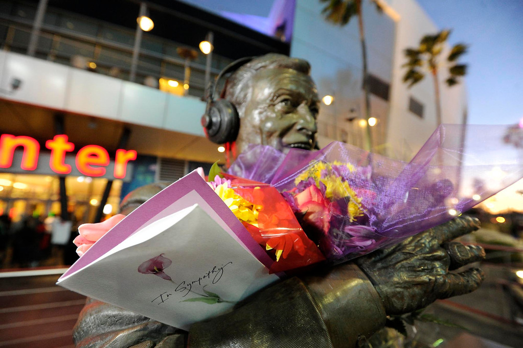 . Flowers were piled around the statue for Chick Hern, in rememberance of Jerry Buss. The Lakers posted large banners around LA Live and Staples Center with a photo of Jerry Buss and plenty of room for fans to write their best wishes. Los Angeles, CA 2/20/2013(John McCoy/Staff Photographer)