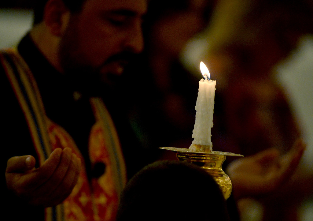 Description of . With candles in the foreground Rev. Father John Saif leads prayer at St. Elias Syriac Orthodox Church in Upland for the two prominent Syrian bishops who have been kidnapped by armed rebels. A Syriac member of the opposition Syrian National Coalition, Abdulahad Steifo, said the men had been kidnapped on the road to Aleppo from the rebel-held Bab al Hawa crossing with Turkey.(Thomas R. Cordova/Staff Photographer)
