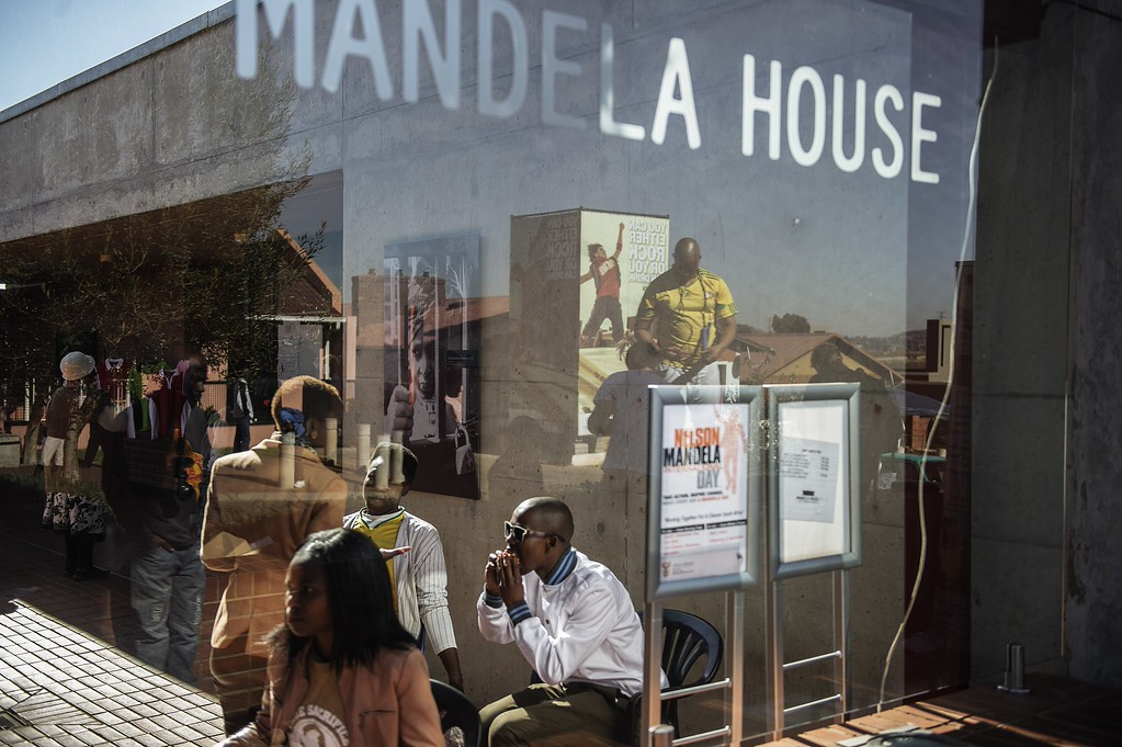 . South African youth sit in the Soweto Mandela House yard as various activities marking International Mandela Day take place in front of the house turned museum of the late global Icon Nelson Mandela on July 18, 2014 in Johannesburg. Mandela Day is a global call to action that celebrates the idea that each individual has the power to transform the world, the ability to make an impact. Nelson Mandela International Day (or Mandela Day) is an annual international day in honour of Nelson Mandela, celebrated each 18 July (on Mandela\'s birthday). The day was officially declared by the United Nations in November 2009, with the first UN Mandela Day held on 18 July 2010.         (GIANLUIGI GUERCIA/AFP/Getty Images)