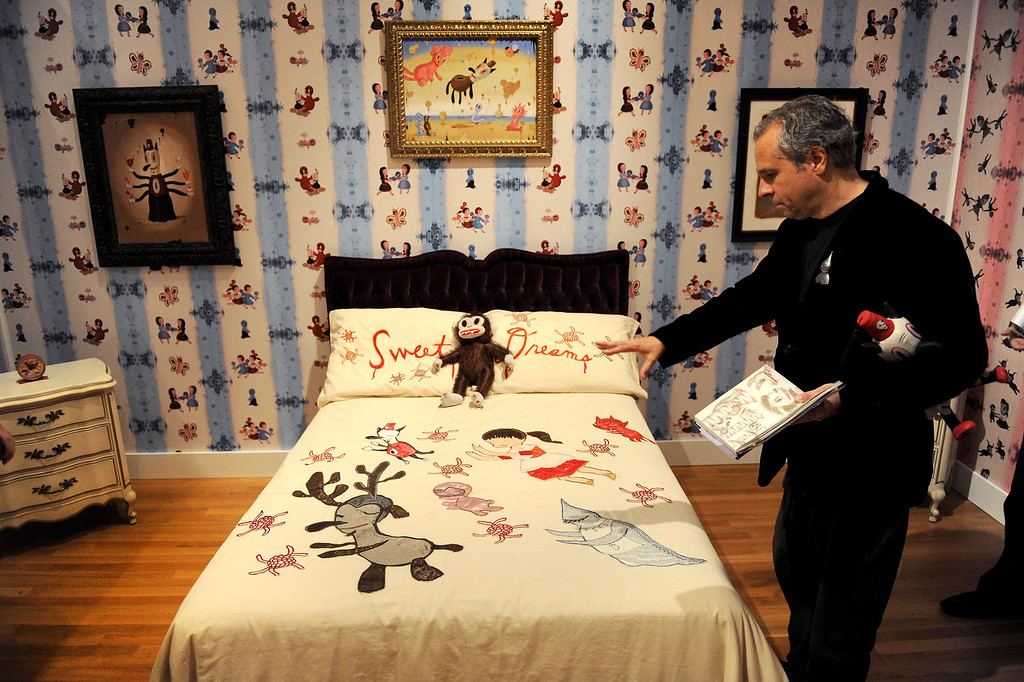 """. Gary Baseman explains the bedroom in the exhibition \""""Gary Baseman: The Door is Always Open,\"""" at the Skirball Cultural Center, Wednesday, April 24, 2013. Baseman\'s work is known for his vibrant, cartoon-like, artistic style in publications such as The New Yorker, Rolling Stone and the LA Times. He designed for the game Cranium and created the animated TV series, Teacher�s Pet.The exhibition design is based on his childhood home in LA�s Fairfax district and includes family furniture and snapshots and many items of interior décor designed by the artist, including wallpaper, pillows, a chandelier and more. (Michael Owen Baker/Staff Photographer)"""