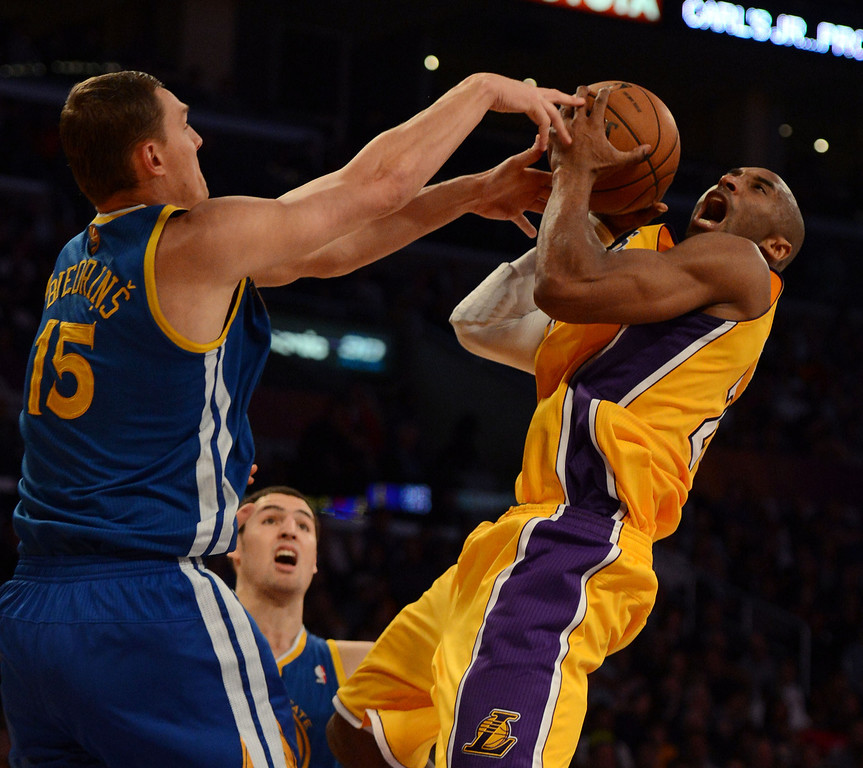 . The Lakers\' Kobe Bryant #24 shoots as the Warriors\' Andris Biedrins #15 defends during their game at the Staples Center in Los Angeles Friday, April 12, 2013. (Hans Gutknecht/Staff Photographer)