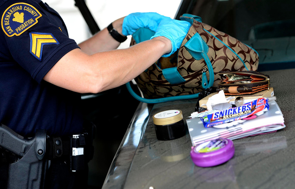Description of . A San Bernardino County Probation officer examines the contents of a purse during a SMASH sweep along the 1200 block of N. Sierra Way in San Bernardino April 4, 2013.   GABRIEL LUIS ACOSTA/STAFF PHOTOGRAPHER.