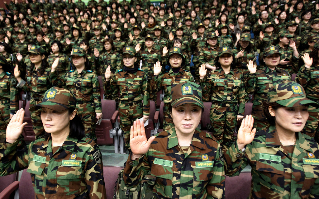 . South Korean army reservists raise their hands to adopt a resolution against North Korea during a rehearsal for their Foundation Day ceremony at a gymnasium in Seoul, South Korea, Friday, April 5, 2013. About 1,000 reservists denounce North Korean for their escalating threat for war. North Korea has been railing against U.S.-South Korean military exercises that began in March and are to continue until the end of this month. The allies insist the exercises in South Korea are routine, but the North calls them rehearsals for an invasion and says it needs nuclear weapons to defend itself. (AP Photo/Ahn Young-joon)