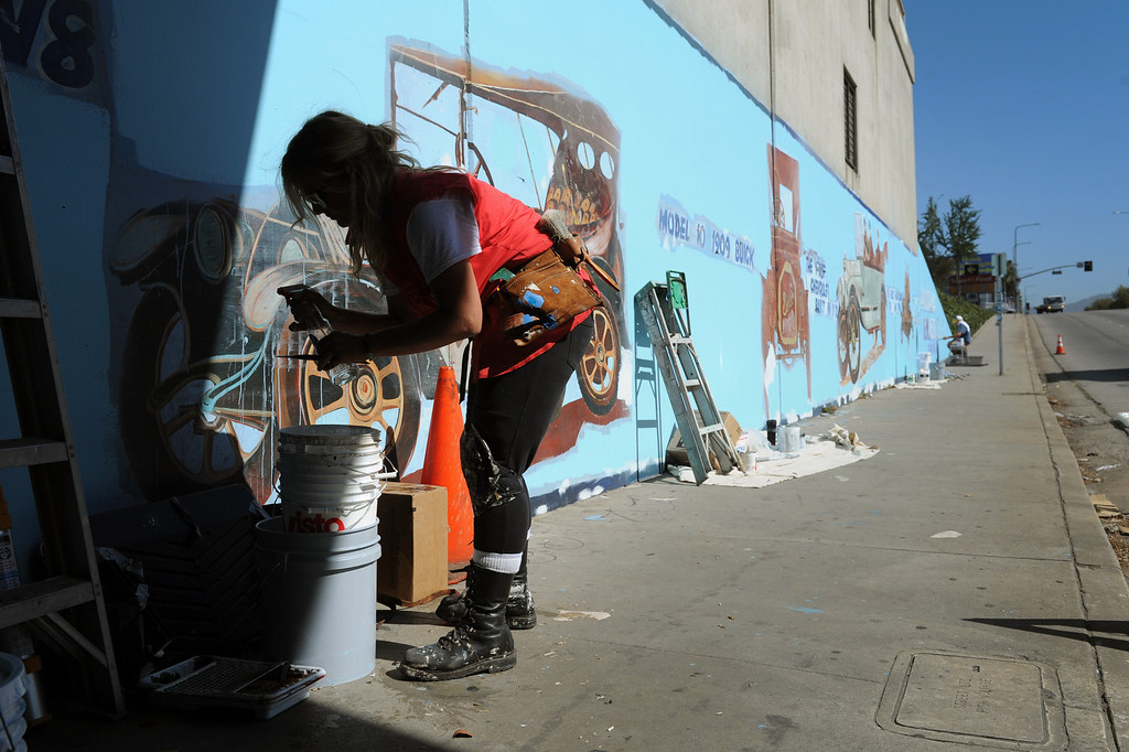 ". Kelly Forbes prepares to paint during restoration of the mural ""Panorama: G.M. Recollections from the Past,\"" on Van Nuys Boulevard in Panorama City, Thursday, June 20, 2013. The original mural was painted by Alfredo Diaz Flores in 1998 and pays homage to the General Motors plant that used to be near the mural site. (Michael Owen Baker/Staff Photographer)"