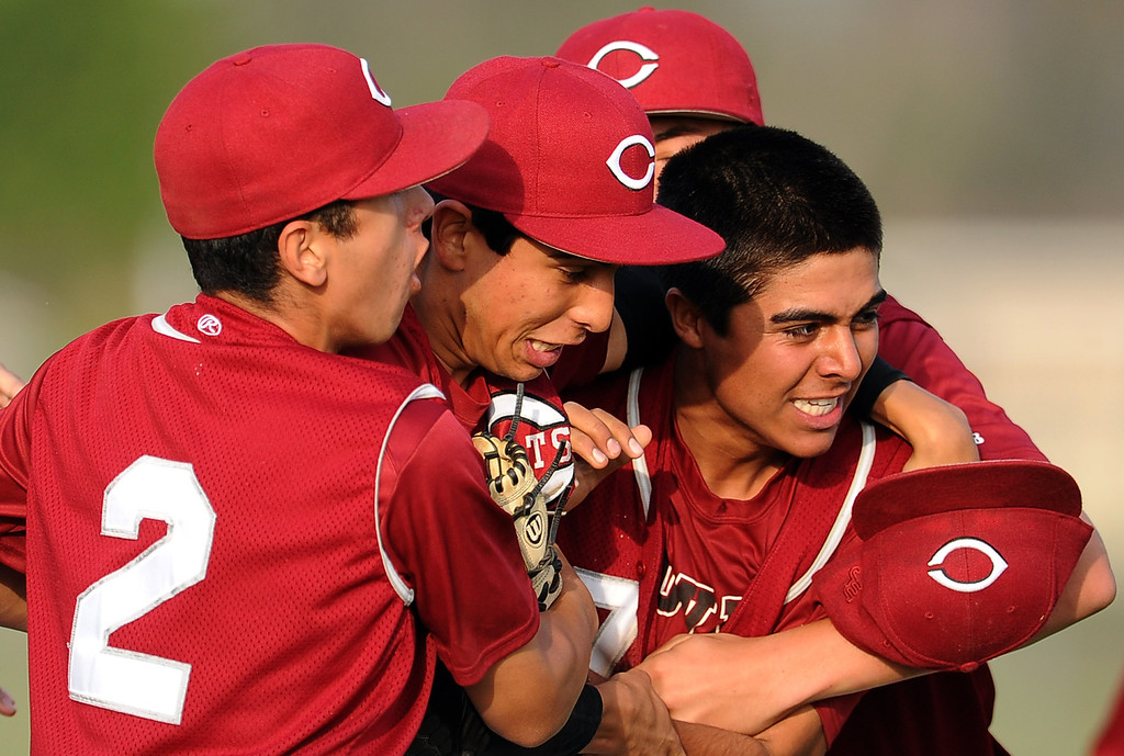 Description of . Covina relief pitcher Joseph Wills, right, is mobbed by teammates after striking out Northview's Adrian Sabatino (not pictured) for the final out of the game as Covina defeated Northview 4-3 during a prep baseball game at Northview High School on Tuesday, March 19, 2013 in Covina, Calif.   (Keith Birmingham Pasadena Star-News)