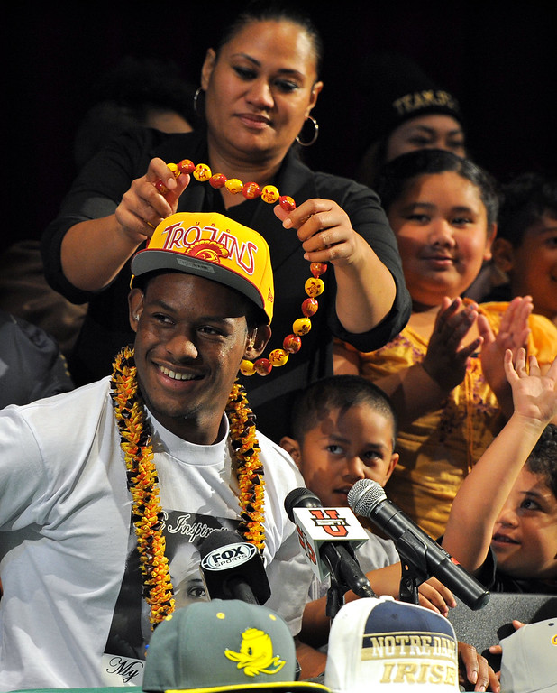 """. Following his announcement that he will play football at USC, Long Beach Poly football player John \""""JuJu\"""" Smith is given USC-colored beads from his mother, Sammy Schuster, in Long Beach, CA on Wednesday, February 5, 2014. (Photo by Scott Varley, Daily Breeze)"""