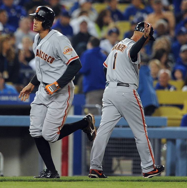 . San Francisco Giants\' Hunter Pence shakes hands with third base coach Tim Flannery (1) after hitting a solo home run in the sixth inning of their baseball game against Los Angeles Dodgers on Wednesday, April 3, 2013 in Los Angeles. 