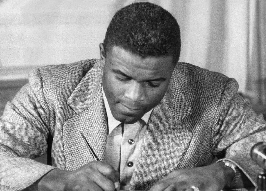 Description of . NEW YORK, UNITED STATES:  Undated photo of US baseball star Jackie Robinson as he signs a then-record contract to play for the Brooklyn Dodgers. Robinson, who endured insults and death threats to integrate United States sports, was honored 15 April by the permanent retirement of his jersey number throughout Major League baseball. The contract, the highest salary in Dodger history up to then, was for US $35 000 a year. (STR/AFP/Getty Images)