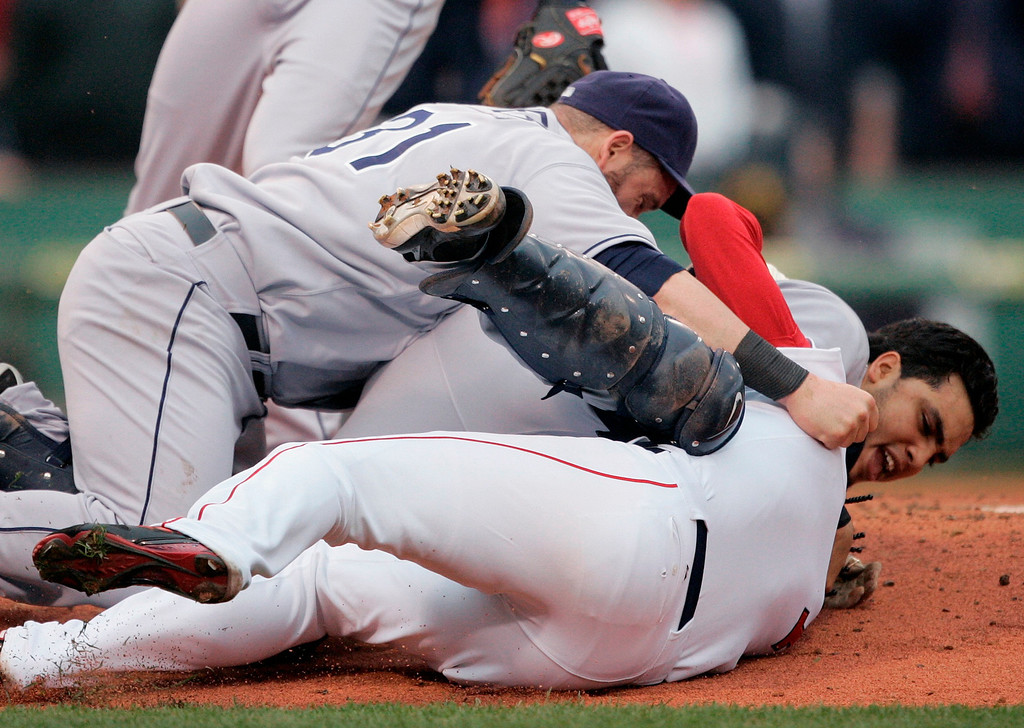 . Tampa Bay Rays\' Jonny Gomes, top left, and Dioner Navarro, middle, fight on the mound with Boston Red Sox\'s Coco Crisp, bottom right, in the second inning of a baseball game, Thursday, June 5, 2008, in Boston. Crisp charged the mound after being hit by a pitch thrown by the Rays\' James Shields which resulted in a bench-clearing brawl between the two teams. (AP Photo/Michael Dwyer)