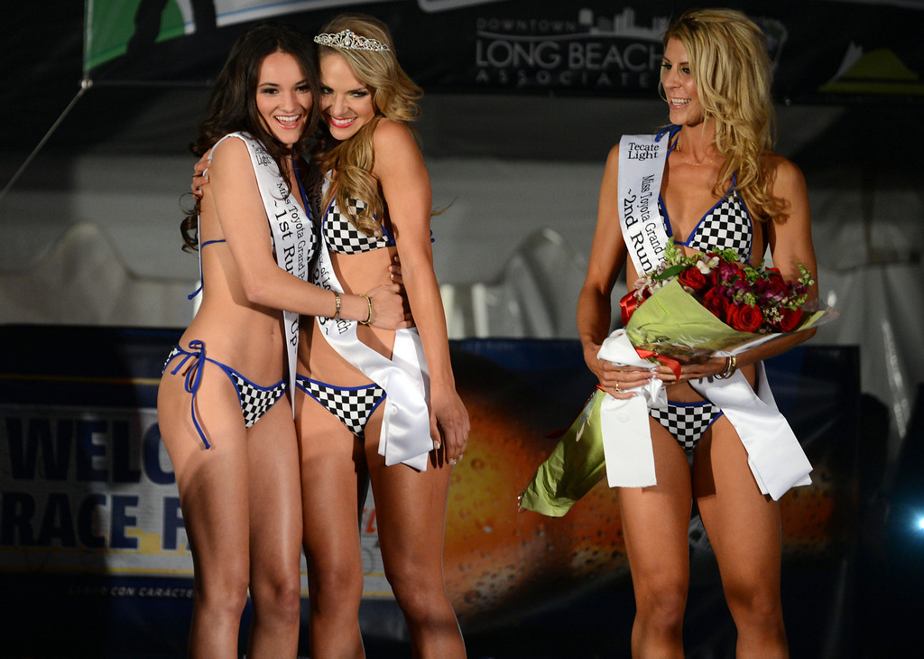 . Long Beach, Calif., -- 04-18-13-  1st runner up emily esparza ,left, gives Lorin Hartwell, newly crowned 2013 Tecate Light Miss Toyota Grand Prix of Long Beach a hug as 2nd runner up Maggie Lane looks on Thursday night on Pine Avenue at the Tecate Light Thunder Thursday on Pine.   Stephen Carr/  Los Angeles Newspaper Group