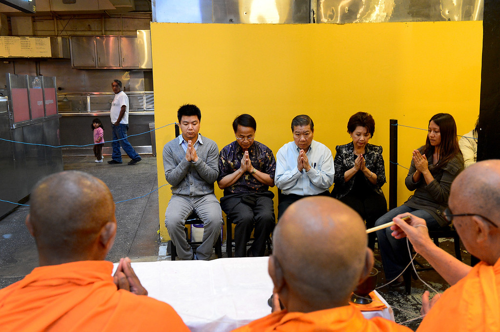 Description of . David Tewasart, left, of Pasadena, and his family follow along in prayer as Wat Thai Temple monks, of North Hollywood, bless the opening of his restaurant Sticky Rice at Grand Central Market in downtown Los Angeles Monday, April 30, 2013.  (SGVN/Staff Photo by Sarah Reingewirtz)
