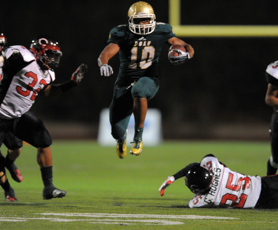 . Long Beach Poly football takes on Centennial (Corona) as part of the Mission Viejo Classic in Mission Viejo, CA on Friday, September 13, 2013. Long Beach Poly won 35-28.  Poly\'s James Brooks leaps over a defender on a big gain. (Photo by Scott Varley, Press-Telegram)