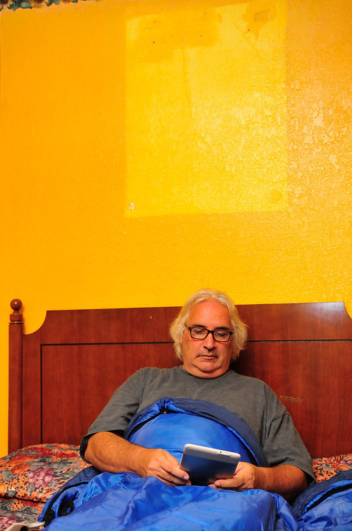 . Reading in bed below a missing picture at the El Capitan Motor Inn.Photo by Thomas Wasper for the Press Telegram