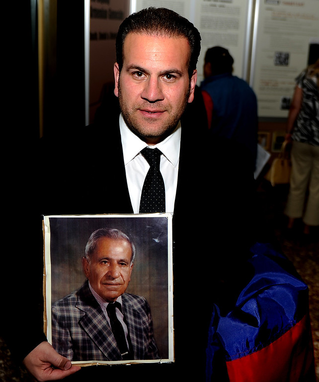 Description of . Jack Hadjinian, city councilman with a photograph of his grandfather Senekerim Arakelian who was part of the genocide with the traveling Armenian Genocide display in the background at the Montebello City Hall on Wednesday, April 10, 2012 in Montebello, Calif. It is the 98th anniversary of the genocide, which occurred between 1915-1923.   (Keith Birmingham/Pasadena Star-News)