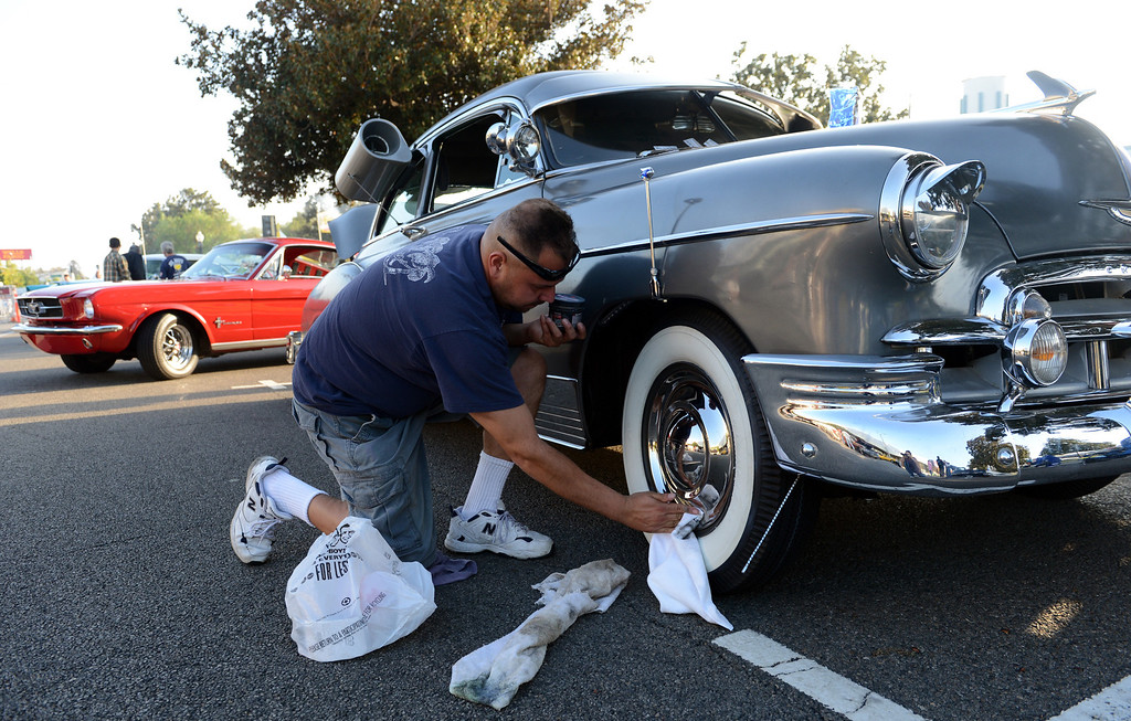 Description of . Andy Braunstein, of West Covina, polishes the hubcaps on his 1950 Chevy at the Route 66 Cruisin' Reunion on Euclid Ave in Ontario, CA Friday, September 20, 2013. (Jennifer Cappuccio Maher/Inland Valley Daily Bulletin)