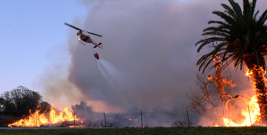 . A helicopter makes a water drop on a fire buring next to the Louis Robidoux Nature Center in the Jurupa Valley on Feb. 28, 2013. As of 7 p.m. approximately 50 acres had burned. (Will Lester/Inland Valley Daily Bulletin)