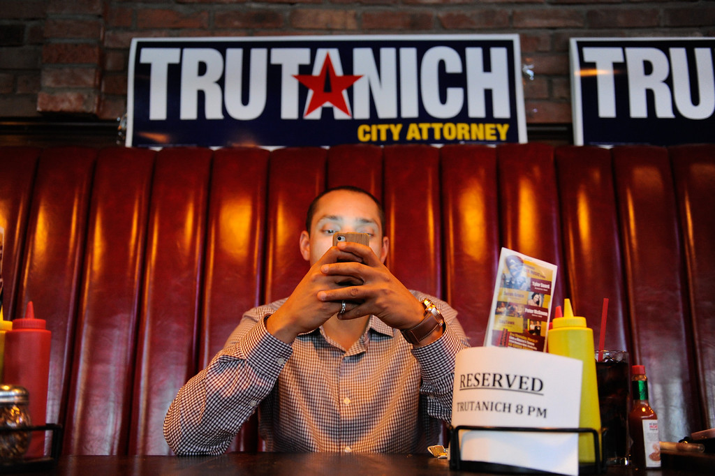 . Jason Dennis checks his smart phone at the Carmen Trutanich campaign party at Rocco\'s Tavern in Studio City, Tuesday, March 5, 2013. (Michael Owen Baker/Staff Photographer)