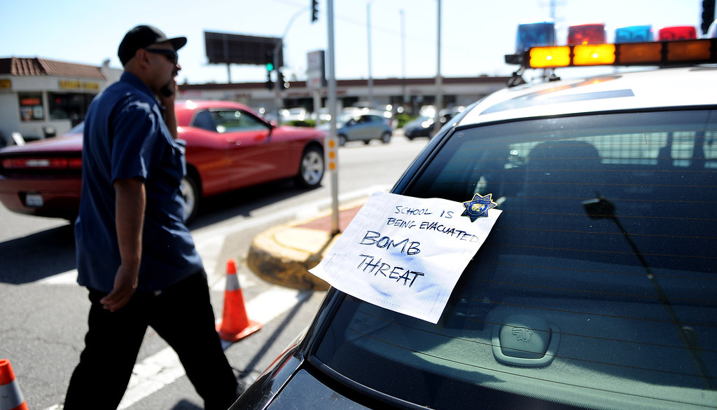 Description of . A man walks by along State University Dr. and Eastern Ave. as a sign on a California Highway Patrol unit reads