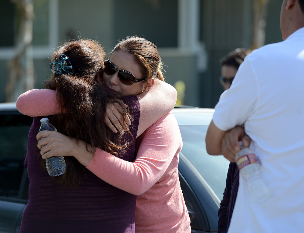 Description of . April Mejia, right, is comforted at the scene as Pomona Police investigate the scene of a murder-suicide in the 2100 block of north Ramsey Way in Pomona, CA, Friday, May 9, 2014. Mejia's mother, sister and brother were murdered by her sister's boyfriend, who then committed suicide.