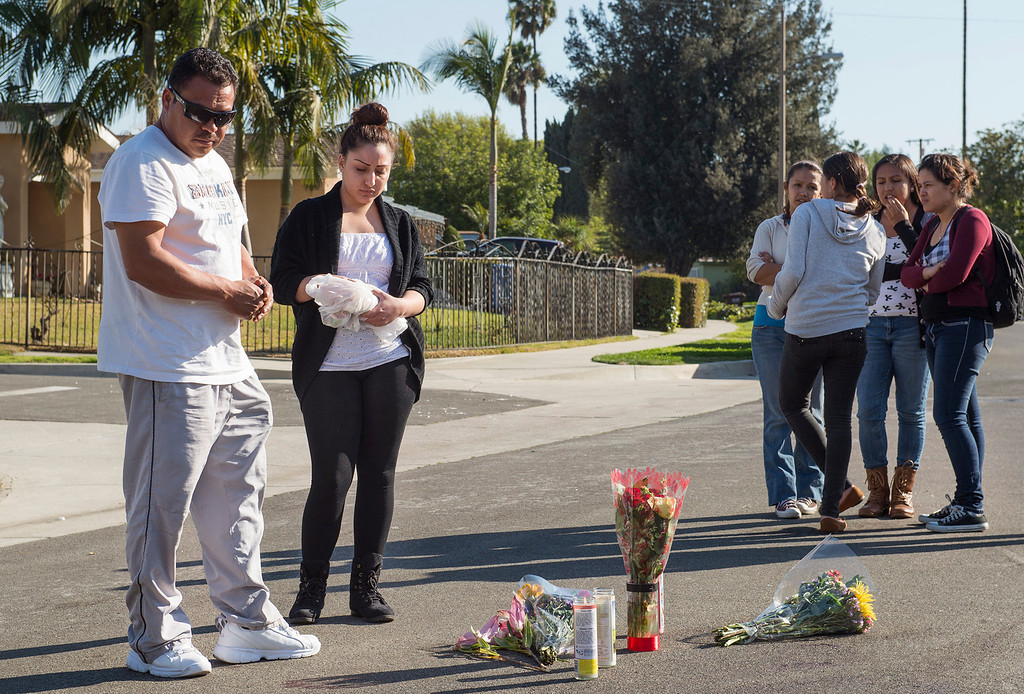 Description of . Mourners gather to place flowers at Wickshire Avenue and Kennard Street--the scene of a hit-and-run homicide that occurred after an altercation at a house party in Hacienda Heights Feb. 25, 2013.   (SGVN/Staff photo by Leo Jarzomb)
