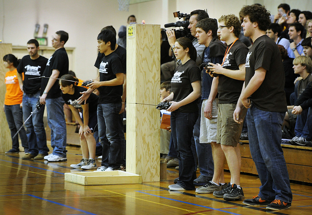 Description of . TEeam Gym Rats, left, with their remote  robot controls competing against Team, How to Train Your Blimp during this year's 28th Annual ME72 Engineering Design Contest,