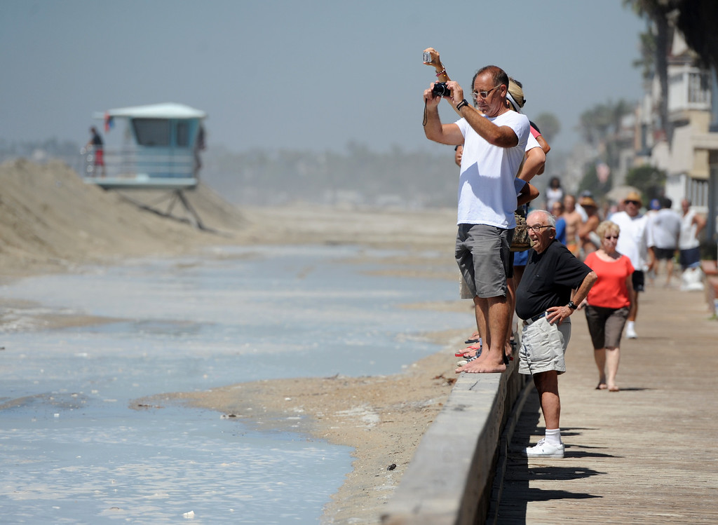 Description of . A crowd lines Seaside Walk in the Peninsula neighborhood to watch crew shore up a sand berm in Long Beach, CA on Wednesday, August 27, 2014. With city crews constantly building a sand berm, the water was held back from the homes and streets during the morning high tide. (Photo by Scott Varley, Daily Breeze)