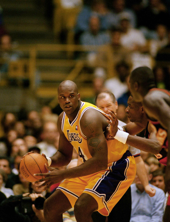 . Los Angeles Lakers center Shaquille O?Neal, left, backs into Atlanta Hawks Dikembe Mutombo, center, during the first quarter action, Jan. 2, 1998 in Inglewood, Calif. O?Neal returned to the Lakers lineup after missing 20 games in the last six weeks due to a fractured wrist and abdominal muscle strain. (AP Photo/Kevork Djansezian)