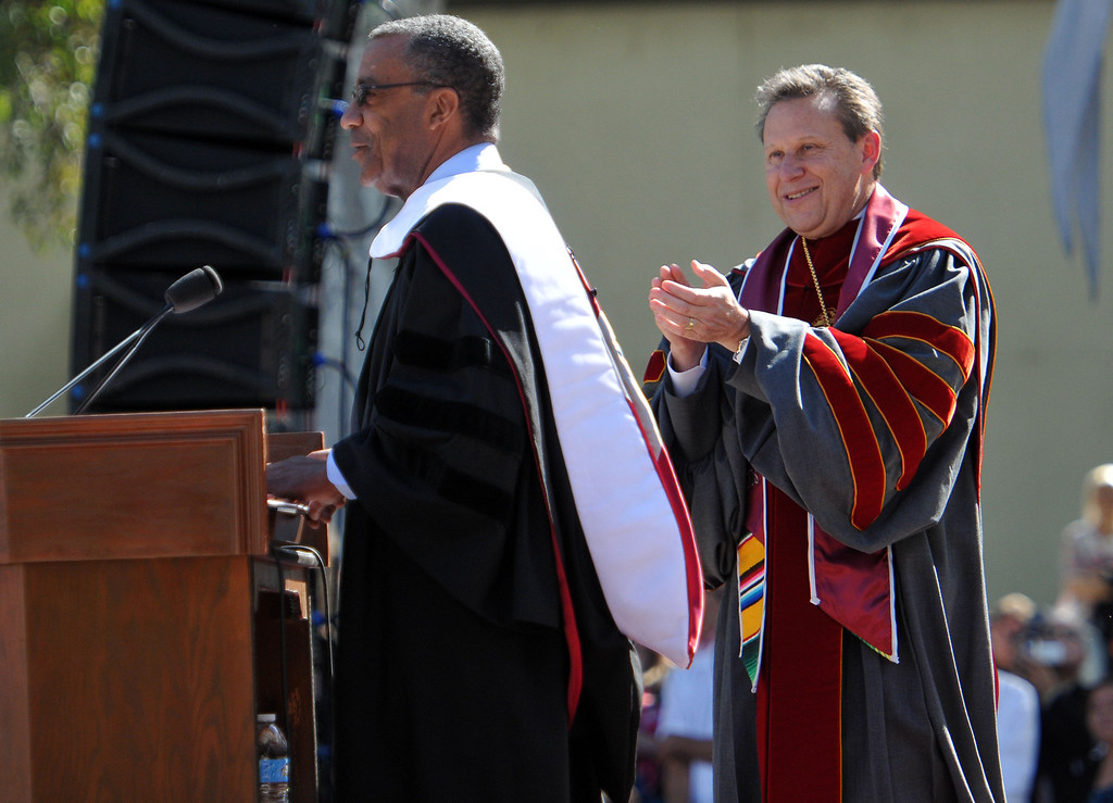 ". (John Valenzuela/Staff Photographer)  University president Ralph Kuncl applauds for Jon Robertson after he receives an honorary doctorate during The 104th College of Arts & Sciences Commencement for the University of Redlands, Saturday, April 20, 2013. University of Redlands alumni, Marilyn Magness Carroll,  delivered the Commencement speech, "" If You Can Dream It, You can Do It\""."