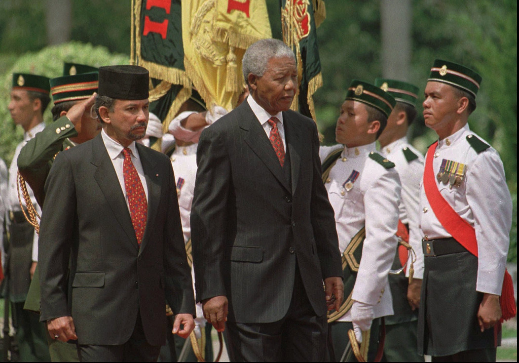 . South African President Nelson Mandela, right, and Sultan Haji Hassanal Bolkiah of Brunei review an honor guard during arrival ceremonies in Bandar Seri Begawan Monday March 3, 1997. Mandela is on a two-day visit to Brunei as part of a four-nation Southeast Asia tour. (AP Photo/Mike Fiala)