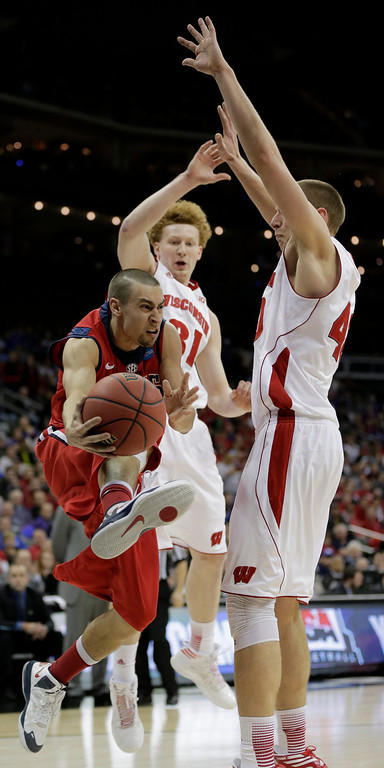 . Mississippi guard Marshall Henderson, left, passes around Wisconsin forward/center Jared Berggren, right, and forward Mike Bruesewitz (31) during the second half of a second-round game of the NCAA college basketball tournament Friday, March 22, 2013, in Kansas City, Mo. (AP Photo/Charlie Riedel)