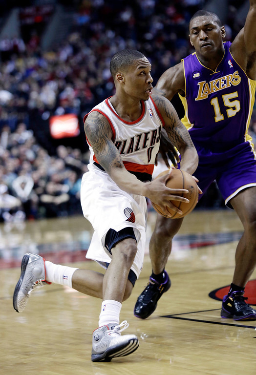. Portland Trail Blazers guard Damian Lillard, left, drives on Los Angeles Lakers forward Metta World Peace during the second half of an NBA basketball game in Portland, Ore., Wednesday, April 10, 2013.  Lillard scored a career-high 38 points as the Lakers won 113-106. (AP Photo/Don Ryan)