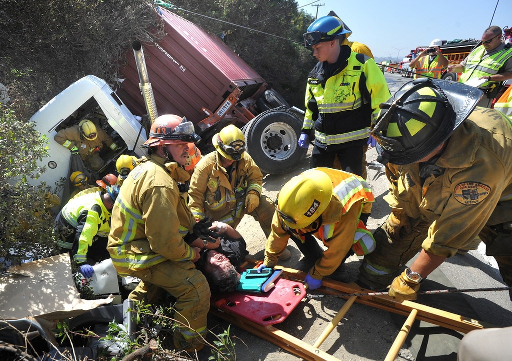 . Los Angeles County firefighters work to extricate the driver from the cab of a tractor trailer that was involved in a four-vehicle collision on the eastbound 60-freeway east of Grand Avenue in Diamond Bar on Wednesday September 18, 2013. The collision involved two trucks and two Caltrans vehicles for a crew that was picking up trash along the freeway. There were eight injuries reported with two of the victims from the tractor trailer taken to a trauma center. (San Gabriel Valley Tribune/Staff Photo by Keith Durflinger)