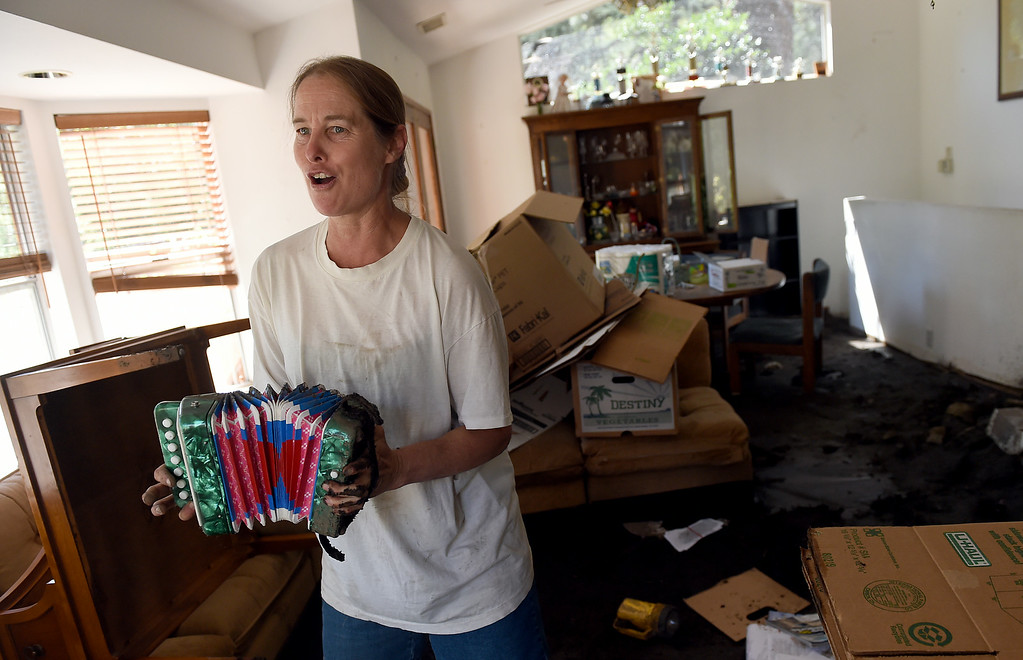 Description of . Michelle Olson plays an accordian and sings about her red-tagged home as she tries to clean-up from Sunday's storm in Mt. Baldy, CA, Tuesday, August 5, 2014. (Photo by Jennifer Cappuccio Maher/Inland Valley Daily Bulletin)