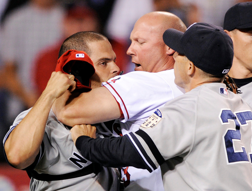 . New York Yankees catcher Ivan Rodriguez, left, is held back by Los Angeles Angels pitching coach Mike Butcher, center, and Yankees manager Joe Girardi  during the sixth inning of a baseball game after a brawl between Rodriguez Angels\' Torii Hunter in Anaheim, Calif., Monday Sept. 8, 2008. (AP Photo/Kevork Djansezian)