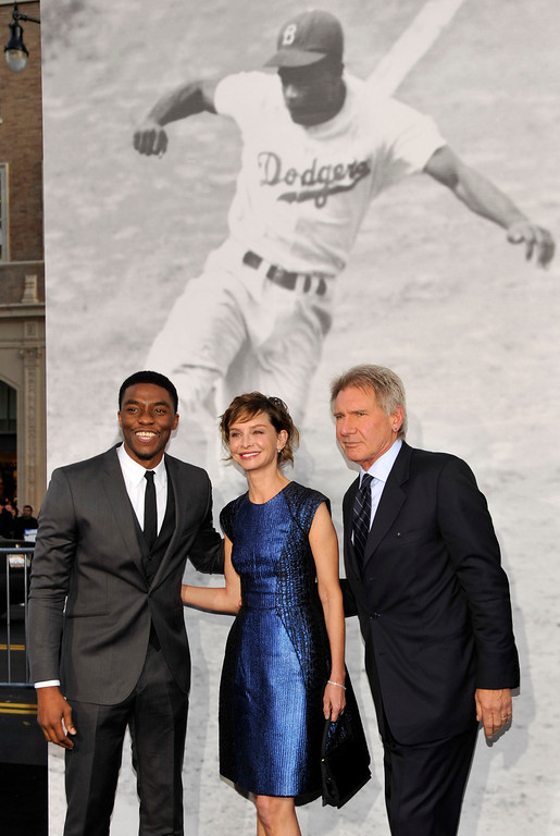 "Description of . Chadwick Boseman, left, who plays baseball legend Jackie Robinson in ""42,\"" poses with fellow cast member Harrison Ford and his wife Calista Flockhart at the Los Angeles premiere of the film at the TCL Chinese Theater on Tuesday, April 9, 2013 in Los Angeles. (Photo by Chris Pizzello/Invision/AP)"