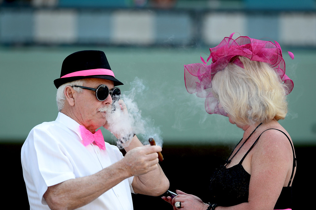 Description of . Paul Burke and Dianne Tanner, of Boston, enjoy the Santa Anita Derby Saturday, April 6, 2013 at Santa Anita Park in Arcadia. Tanner picks the horses and the colors as the two  follow the races across the county. (SGVN/Staff Photo by Sarah Reingewirtz)