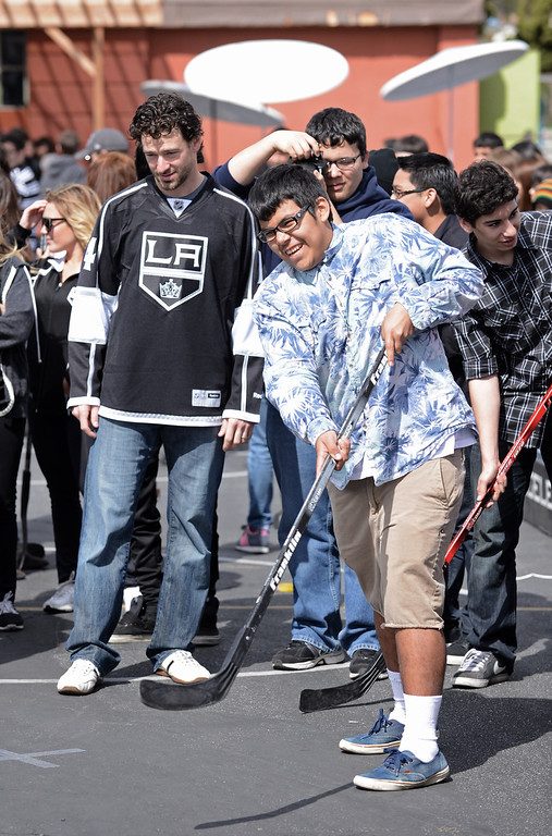 . LA Kings player Justin Williams, #14, watches Martin Correa, 10th grade make a shot on goal at DaVinci High School in Hawthorne.   Photo by Brad Graverson 3-8-13