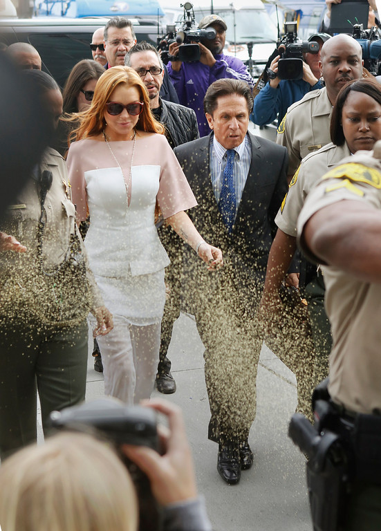 . Actress Lindsay Lohan is showered with gold glitter, left, as she walks with her attorney Mark Heller, to attend a trial Monday, March 18, 2013, at  Los Angeles Superior court. Lohan is charged with three misdemeanor counts stemming from a crash on Pacific Coast Highway. She is charged with willfully resisting, obstructing or delaying an officer, providing false information to an officer and reckless driving. She is also accused of violating her probation in a misdemeanor jewelry theft case. (AP Photo/Damian Dovarganes)