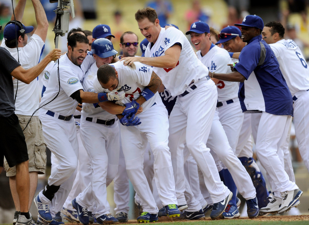 . The Dodgers Matt Kemp is mobbed by teammates at home plate after hitting a two-run homer in the 12th inning that beat the Phillies 5-3, Wednesday, July 18, 2012, at Dodger Stadium. (Michael Owen Baker/Staff Photographer)