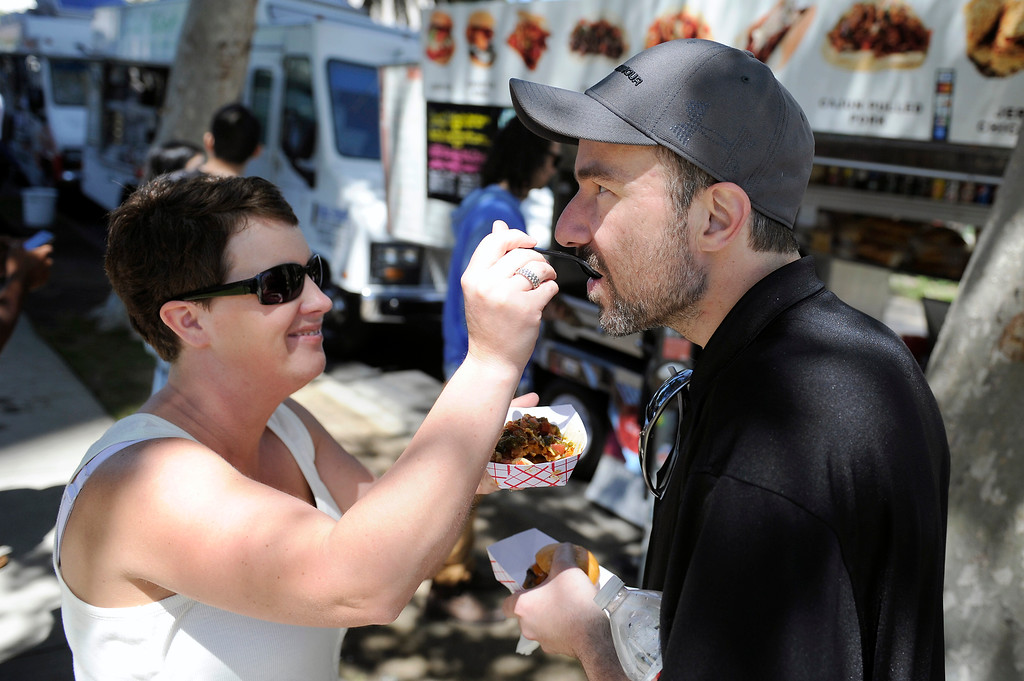 . Lisa Henderson shares her fish taco with her husband Curtis Henderson by the food trucks on Wilshire Boulevard across from the Los Angeles County Museum of Art, Wednesday, April 10, 2013. (Michael Owen Baker/Staff Photographer)