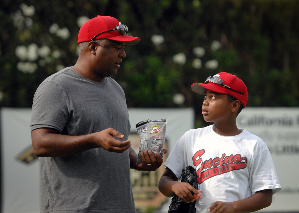 . Rodney Peete talks with his son Robinson during practice for Encino\'s 11-under all-star baseball team. (Michael Owen Baker/L.A. Daily News)