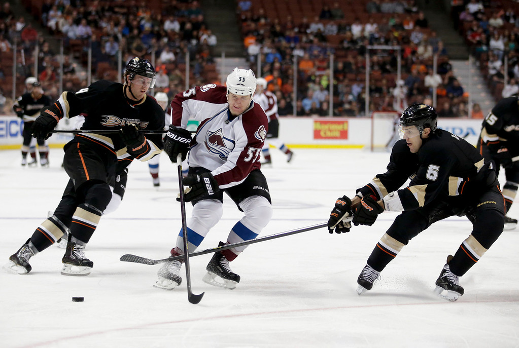 . Colorado Avalanche\'s Cody McLeod, center, has the puck poked away by Anaheim Ducks\' Ben Lovejoy, right, during the first period of an NHL hockey game in Anaheim, Calif., Wednesday, April 10, 2013. (AP Photo/Jae C. Hong)