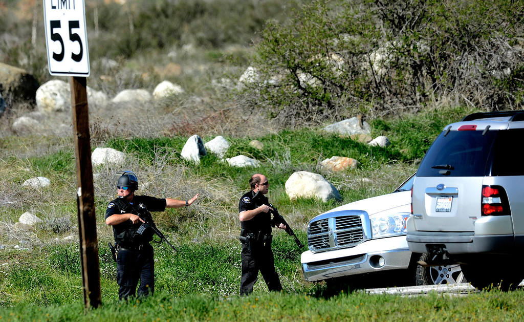 . Redlands Police officers execute a blockade at Highway 38 and Bryant Street near the Mill Street Ranger Station west of Yucaipa February 12, 2013.  Authorities believe that they exchanged gunfire with fugitive Christopher Dorner in the Barton Flats area of the San Bernardino National Forest.  Fish and Game officers spotted a man fitting the description of Dorner driving a white pick-up, and two San Bernardino County Sheriff Deputies exchanged gunfire with him.  Hundreds of shots have been fired, and the two deputies were injured.  GABRIEL LUIS ACOSTA/STAFF PHOTOGRAPHER.