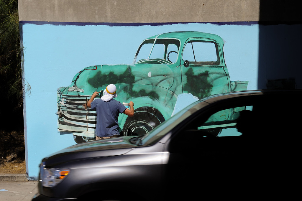 ". Cars whiz by Jeff Lingle painting the restoration of the mural ""Panorama: G.M. Recollections from the Past,\"" on Van Nuys Boulevard in Panorama City, Thursday, June 20, 2013. The original mural was painted by Alfredo Diaz Flores in 1998 and pays homage to the General Motors plant that used to be near the mural site. (Michael Owen Baker/Staff Photographer)"