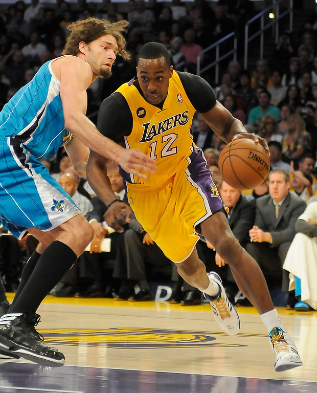 . Lakers#12 Dwight Howard drives around Hornets#15 Robin Lopez in the first quarter.  The Lakers played the New Orleans Hornets at Staples Center in Los Angeles CA 4/9/2013(John McCoy/Staff Photographer