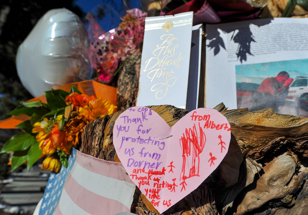 . Over the last couple of days a makeshift memorial as grown near a wood-carved bear at the Sheriff\'s Station in Big Bear on Thursday, Feb. 14, 2013. Valentine\'s Day cards, sympathy cards, balloons and flowers paid tribute to the law enforcement personnel who were involved and lost in the Christopher Dorner manhunt. (Rachel Luna / Staff Photographer)