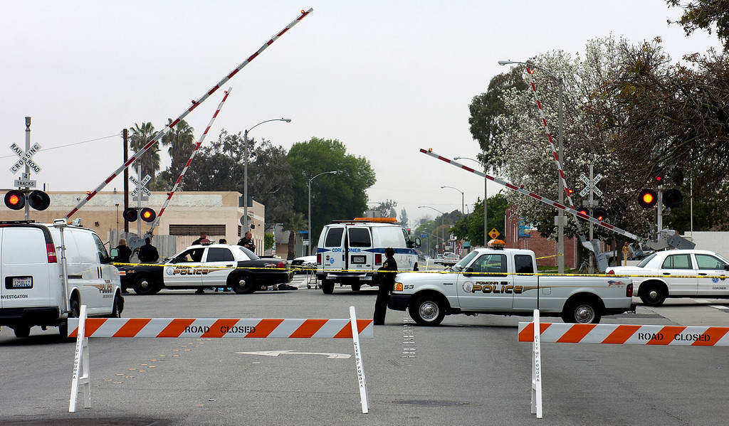 Description of . Pomona Police investigate the scene where a pedestrian was hit and killed by a train Wednesday, March 27, 2013, at Park Ave and First Street in Pomona. Jennifer Cappuccio Maher/Staff Photographer