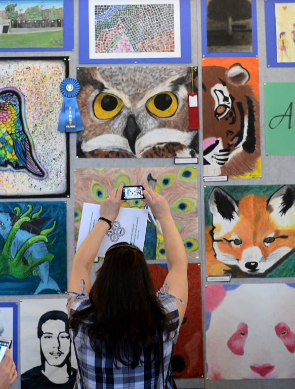 . A parent takes a photo of a painting of a owl as Upland High School\'s visual and performing arts students showcase their work during their annual show in Upland April 26, 2013. (Thomas R. Cordova/Staff Photographer)