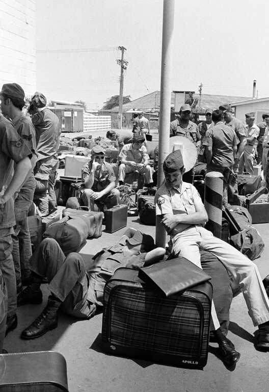 Description of . An American GI takes a nap atop his luggage as he and other troops wait to begin outprocessing at Camp Alpha in Saigon, March 27, 1973, as withdrawal of U.S. troops resume after a 10-day dispute over POWs.  All U.S. troops are due out Thursday.  (AP Photo/Chick Harrity)